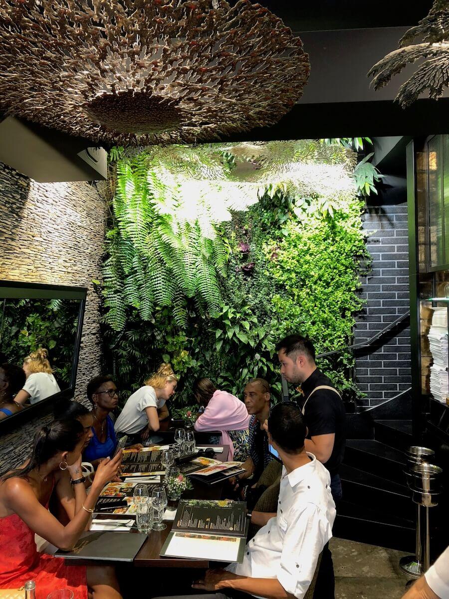 petit restaurant avec un mur végétal au fond
